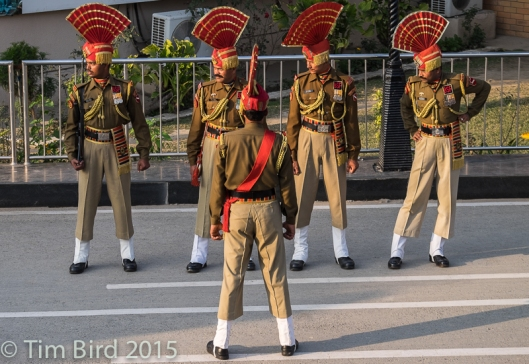 The ceremony of closing of the border with Pakistan near Amritsar has become a tourist attraction. The soldiers are staring towards Pakistan, where a similarly flamboyant guard contingent is staring back at them.