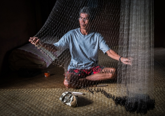 Mending nets at a Longhouse community in Sarawak, Borneo, Malaysia.